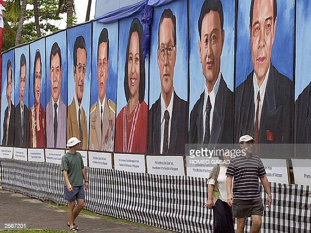 Three tourists walk by a huge portraits of the leaders of the 10 ASEAN member countries displayed in Nusa Dua on Bali island 06 October 2003 The...