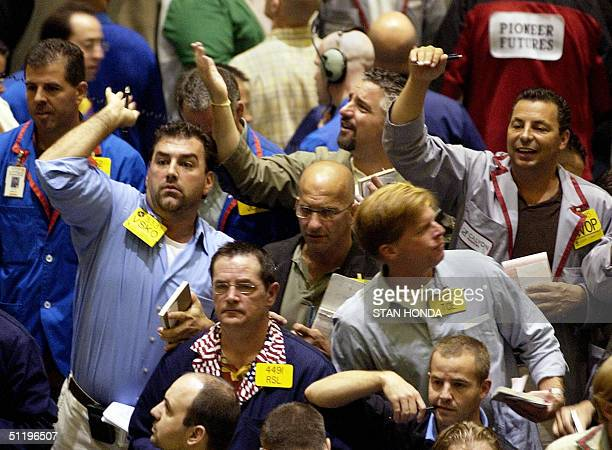 Three traders gesture and shout for attention in the crude oil futures pit 20 August on the floor of the New York Mercantile Exchange World oil...