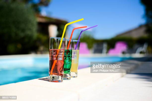 Three tropical colorful drink cocktail with straw on the poolside of resort swimming pool with nobody.