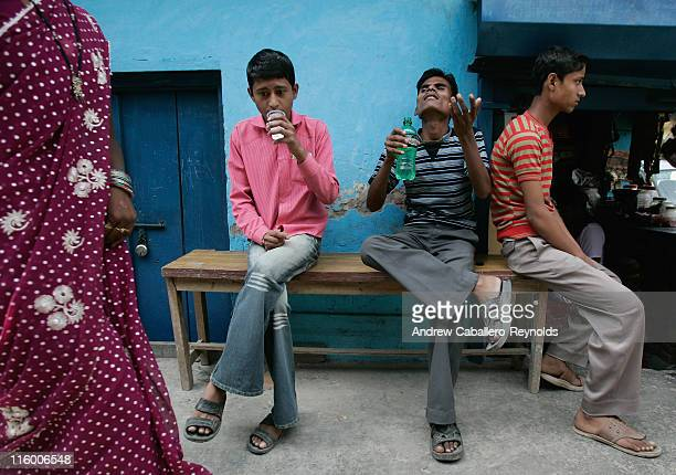 Three tuberculosis patients sit on a bench as they wait and take their medication at an operation ASHA treatment center set up in a small shop on...