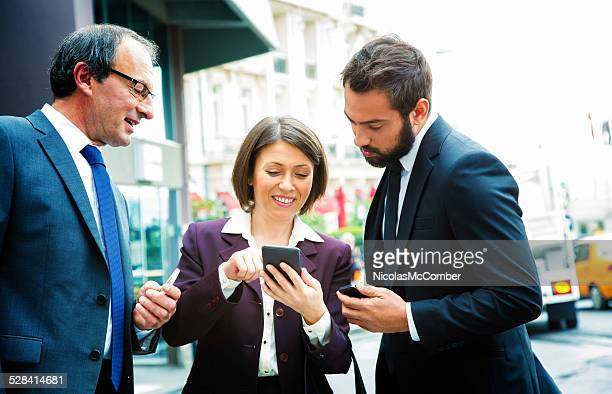 Three Turkish business people sharing information on their phone