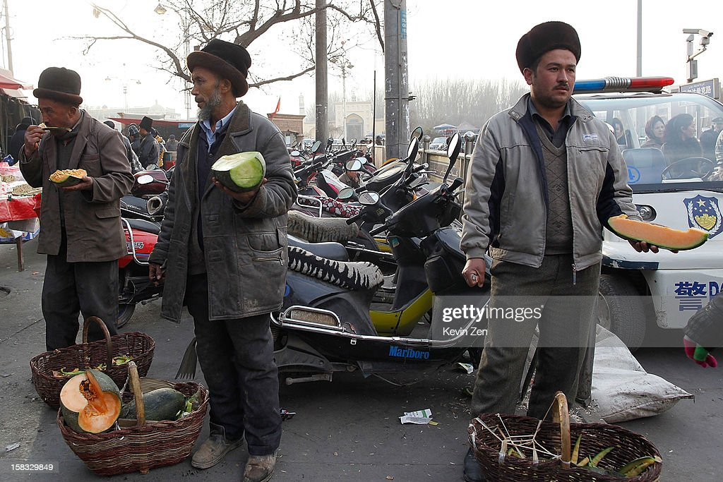 Three Uighur vendors in the street selling watermelon in Kashgar, on December 10, 2012 in Kashi, China. Kashgar is home to the ethnic Uyghur Muslim community.