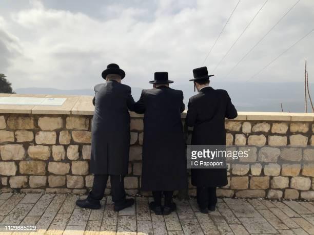 Three Ultra Orthodox Jews pray at a wall on February 7 2019 in Safed Israel
