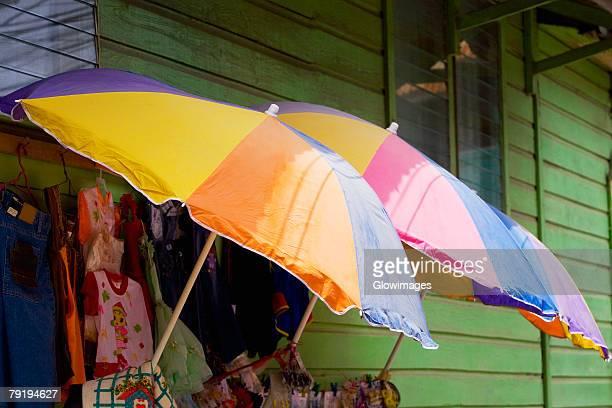 Three umbrellas with clothes in a clothing store, Coxen Hole, Roatan, Bay Islands, Honduras