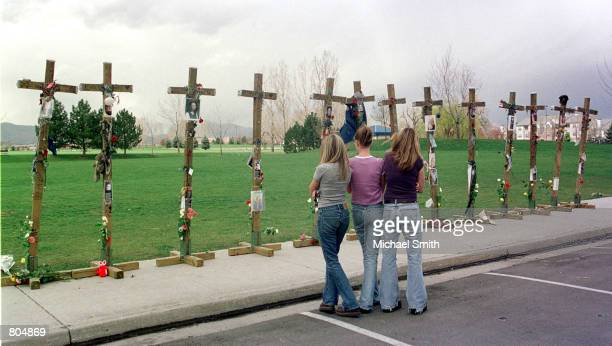 Three unidentified Columbine High School students look at the 13 crosses memorializing those killed at their school 2 years ago after a memorial...