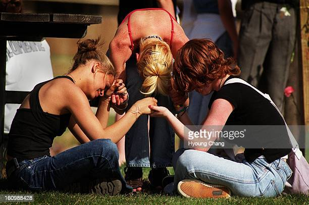 Three unidentified girls weep in the First Amendment area of Clement Park on the one year anniversary of the tragic Columbine High School Shootings