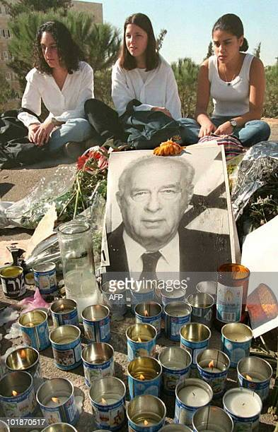 Three unidentified Israeli girls sit in front of the Israeli parliament next to a memorial of candles and flowers for Israel's assassinated Prime...