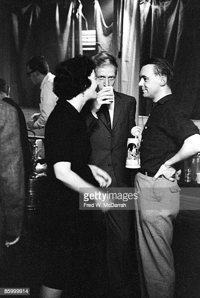 Three unidentified people two men and a woman talking among themselves at a party New York New York April 2 1960
