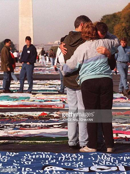Three unidentified visitors comfort each other while thousands of friends and family members of AIDS victims visit the AIDS Memorial Quilt displayed...