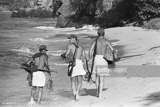 Three United States Army soldiers stroll on a Grenada beach during the 1983 invasion The soldiers only wear towels and carry machine guns | Location...