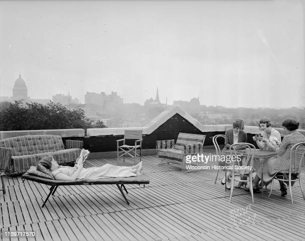 Three University of WisconsinMadison coeds are playing cards and one woman is reading on the roof of Ann Emery Hall 265 Langdon Street an independent...