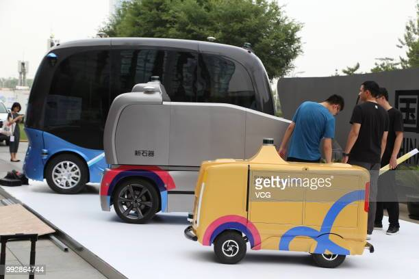 Three unmanned vehicles, that use Baidu's Apollo autonomous driving system, are on display during the Baidu Create 2018 at China National Convention...
