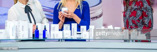 three unrecognizable women discussing cosmetic products on tv show - saleswoman stock photos and pictures