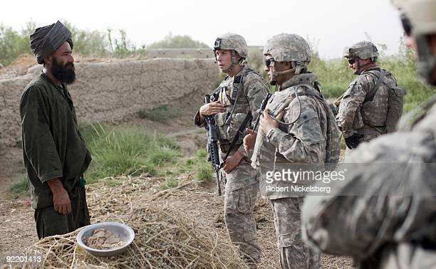 Three US Army soldiers associated with the Psychological Warfare unit speak through an interpreter to an afghan farmer in Khan Neshin Afghanistan...