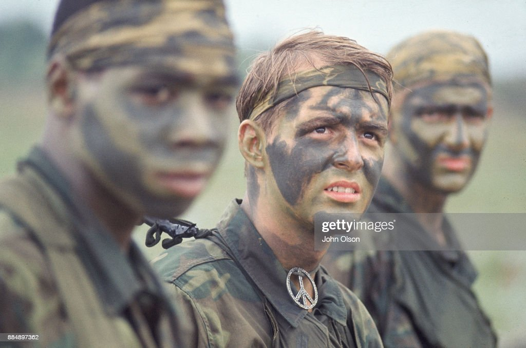 Three US Army soldiers wearing camouflage uniforms and face paint