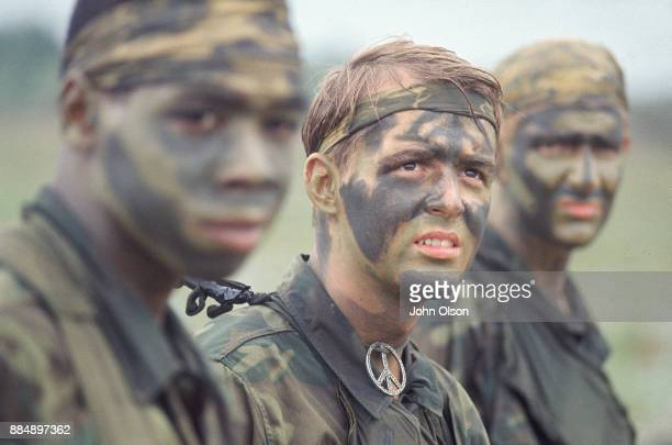 Three US Army soldiers wearing camouflage uniforms and face paint Vietnam 1968 Soldier in focus is wearing a peace symbol necklace