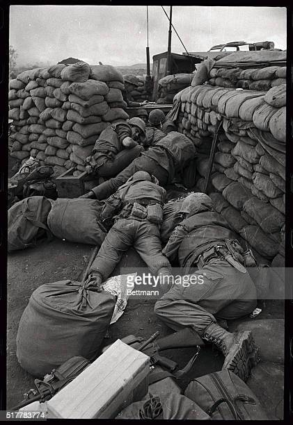 Three US Marines just arriving as reinforcements at the besieged Marine stronghold at Khe Sanh drop their duffel bags and other equipment and run for...