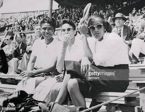 Three US Olympic athletes watch other Olympic stars as they take it easy from the spectator stands at Wembley Stadium July 31st Left to right are...