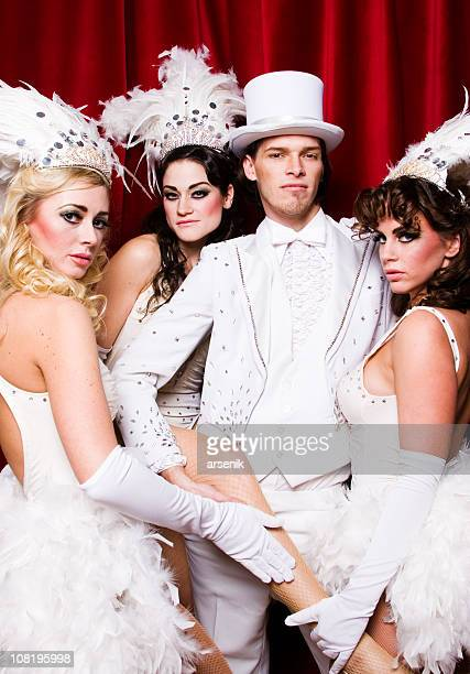 Three Vegas Showgirls Posing with Male Master of Ceremony