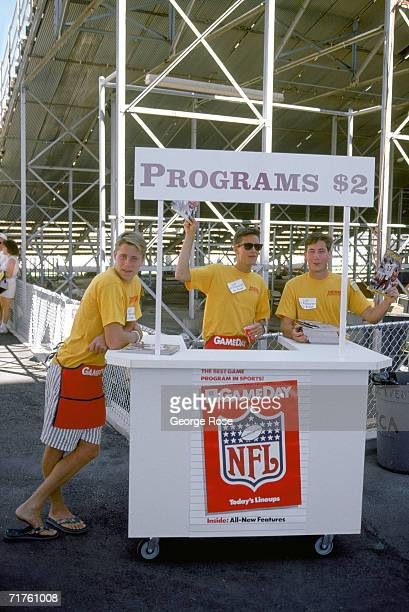 Three vendors selling programs stands at a booth before the game of the Washington Redskins against the Phoenix Cardinals at the Sun Devil Stadium on...