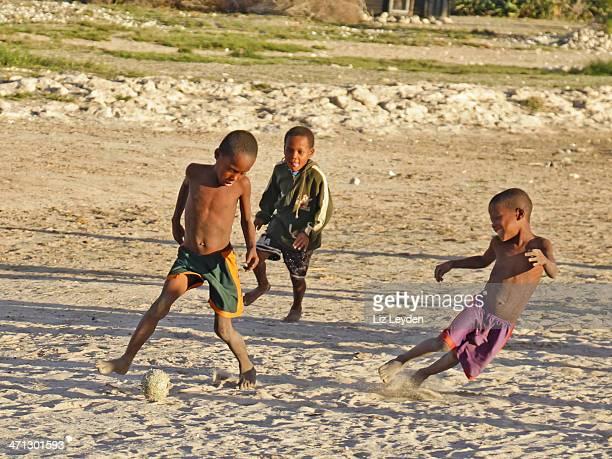 trois culture vezo garçons jouant au football sur la plage: anakao, madagascar - madagascar enfant photos et images de collection