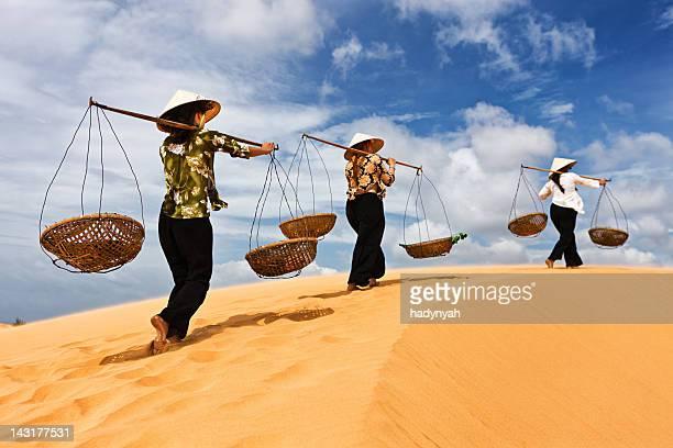 Three Vietnamese women crossing sand dunes