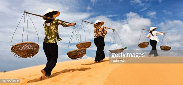 three vietnamese women crossing sand dunes - traditionally vietnamese stock pictures, royalty-free photos & images