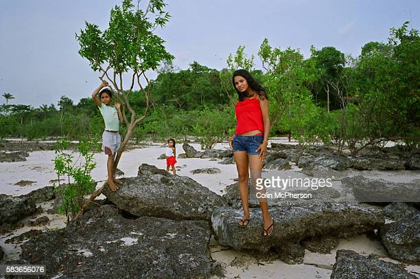 Three village girls standing on rocks on the beach near their home by the Tapajos river The Floresta Nacional do Tapajos a 6500 km2 protected reserve...