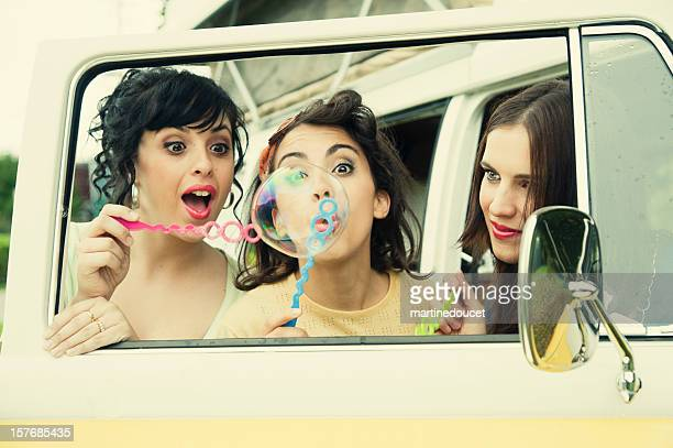 Three vintages girls blowing bubbles through open car door.