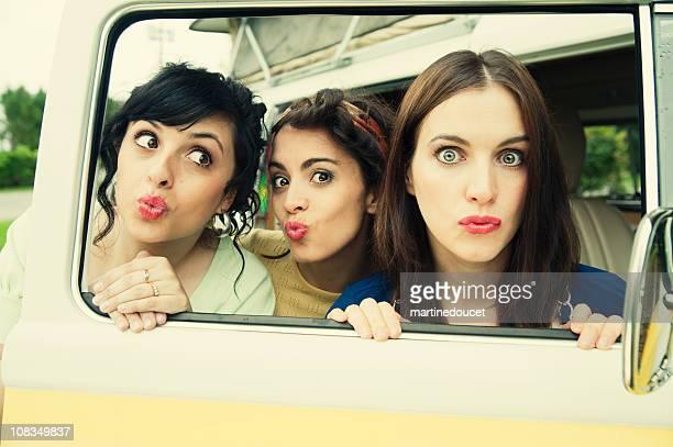 Drei Sorten Mädchen Blasen Küsse durch eine offene dem Auto entfernt.
