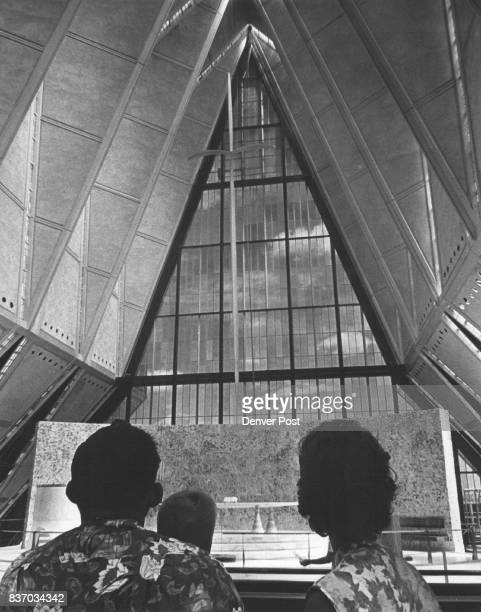 Three visitors from Phoenix gaze up at the huge cross above the freestanding altar in the Protestant Chapel in the Air Force Academy's Cadet Chapel...