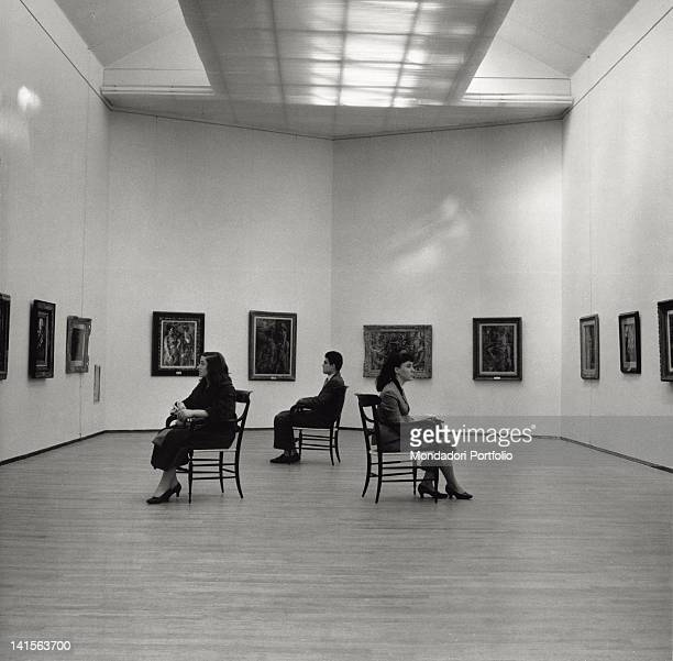 Three visitors of the Modern Art Gallery of Milan are looking at the works of the exhibition of paintings of the French painter Georges Rouault Milan...