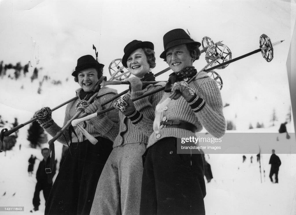 Three visitors to St. Moritz, the popular Swiss Winter sports resort, wearing Tyrolean hats. Switzerland. Photograph. Around 1935.