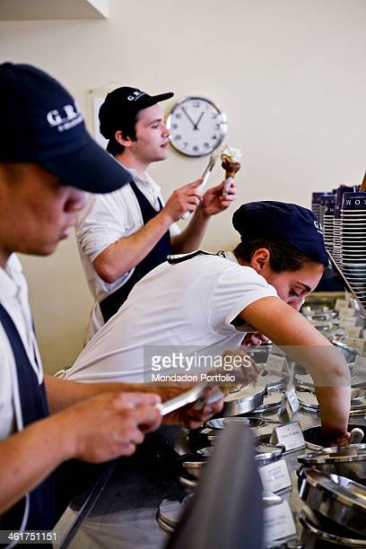 Three waiters preparing icecream cones at the bar of the Grom icecream shop Milan Italy 2013