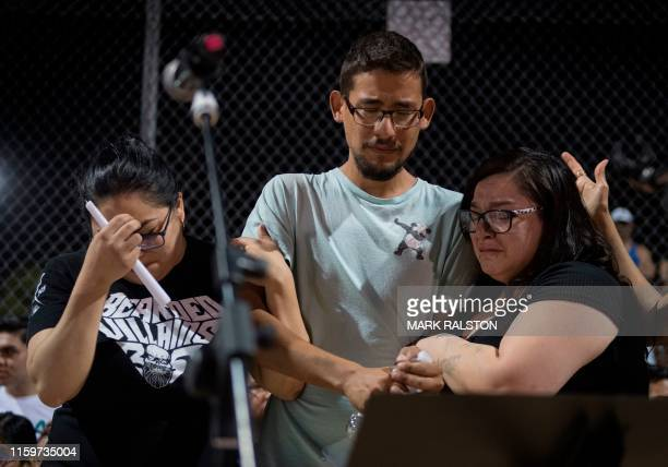 Three Walmart employees who were present during the shooting react on stage during a prayer and candle vigil organized by the city after a shooting...