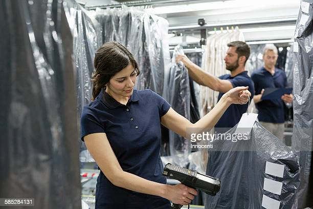 Three warehouse workers doing garment stock take in distribution warehouse
