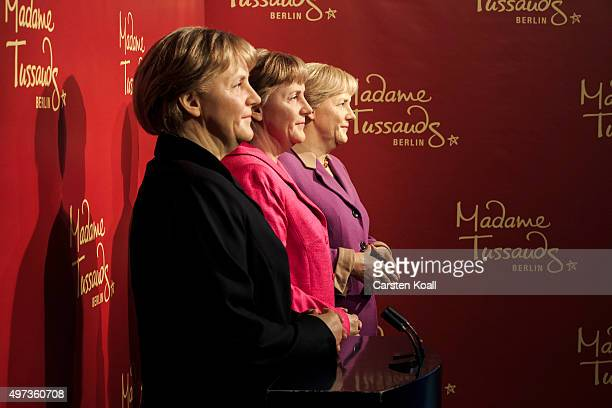 Three wax figures of German Chancellor Angela Merkel stand at Madame Tussauds on November 16 2015 in Berlin Germany The figures brought together from...