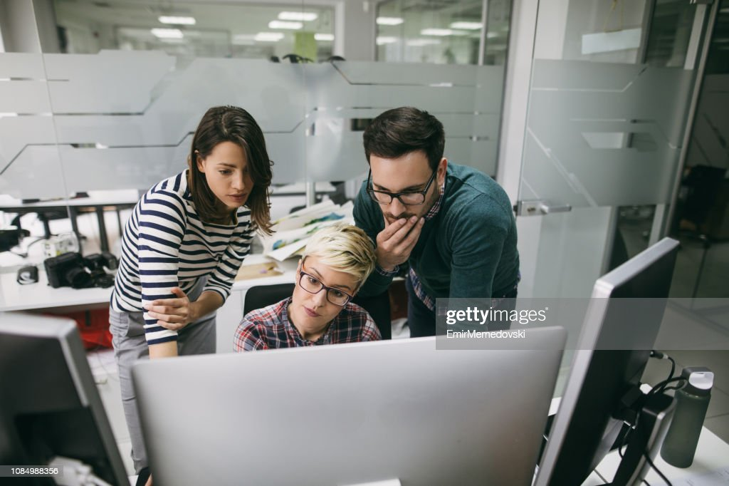 Three web designers working in office on a project together : Stock Photo