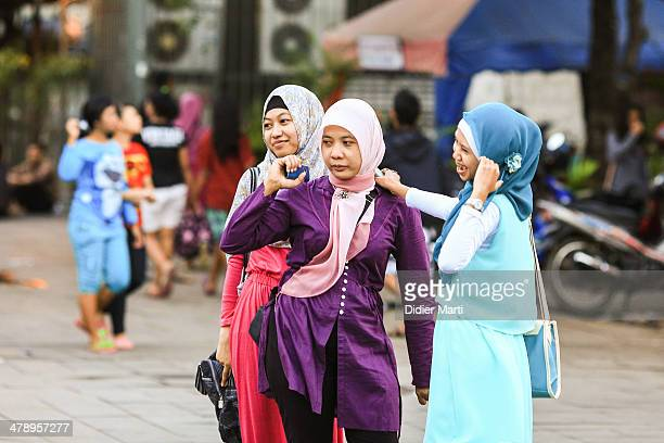 Three well dressed muslim women in the streets of Jakarta in Indonesia