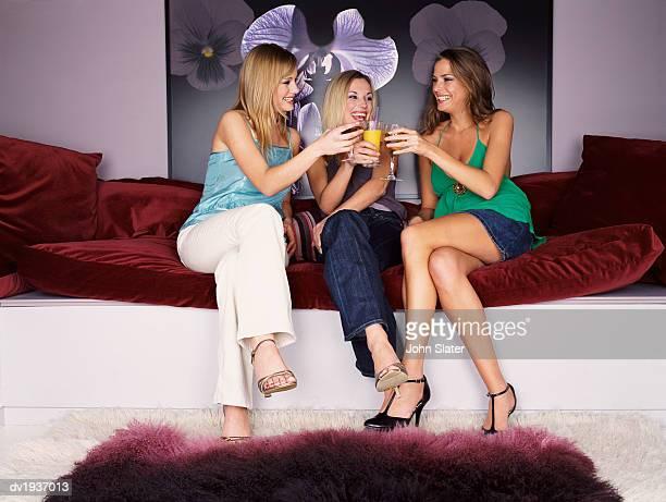 Three Well-Dressed Teenage Girls Sit on a Sofa, Making a Toast
