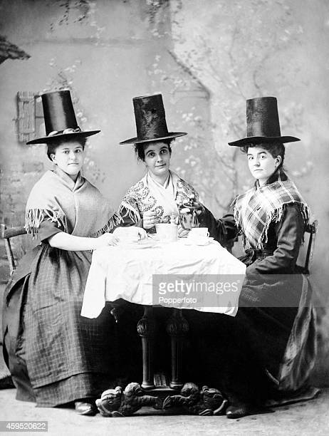 Three Welsh women wearing typical hats of the period and drinking tea in a studio setting circa 1890