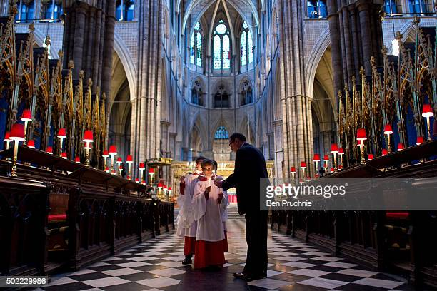 Three Westminister Abbey choristers have their candles lit ahead of posing for photographs in Westminster Abbey on December 21 2015 in London England...
