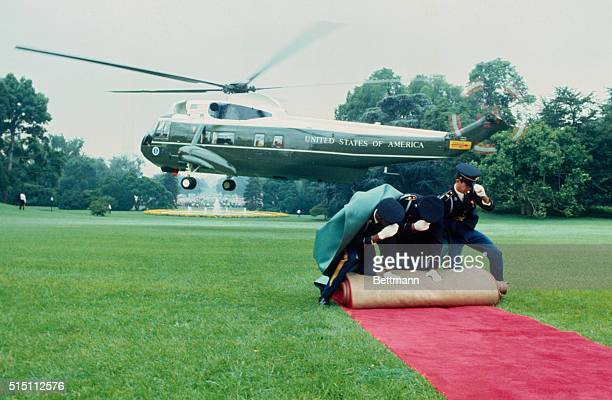 Three White House guards rollup the red carpet as President Nixon leaves in a helicopter after resigning