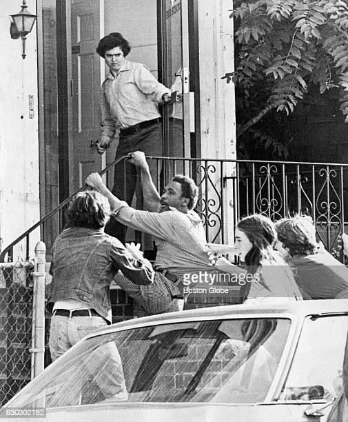 Three white people surround JeanLouis Andre Yvon pulling on his clothing in front of a house on Dochester Street in Boston Mass on Oct 7 1974 Yvon...