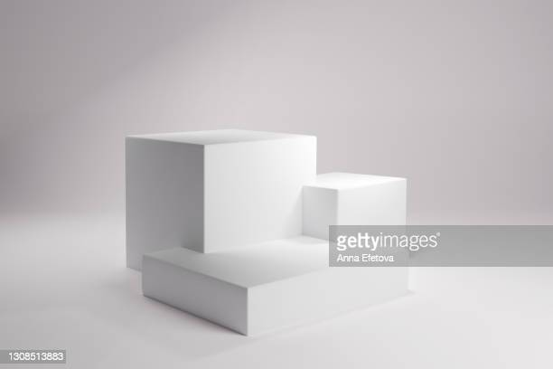 three white square podiums or stages for cosmetics over clean background with sun light. perfect for demonstrating your product. front view. three dimensional - podio del ganador fotografías e imágenes de stock