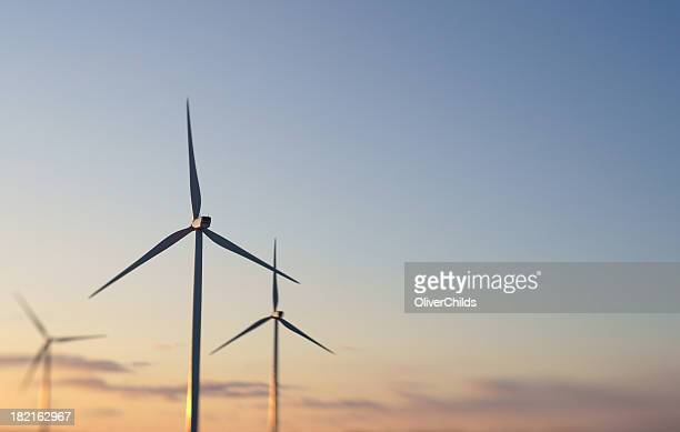 Three wind turbines at sunset.