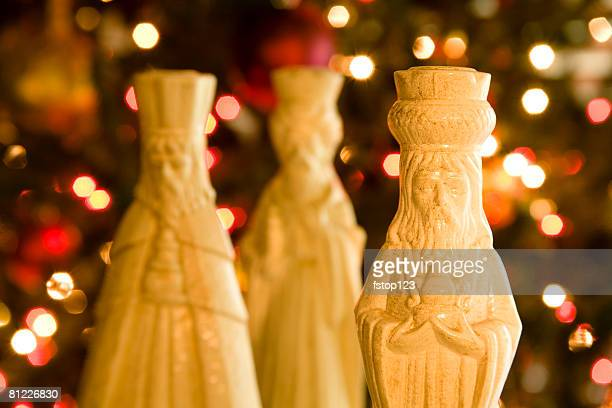 three wisemen in front of a christmas tree.  selective focus on king in front. - three wise men stock photos and pictures