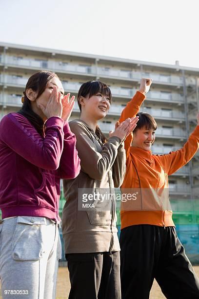 Three woman cheering