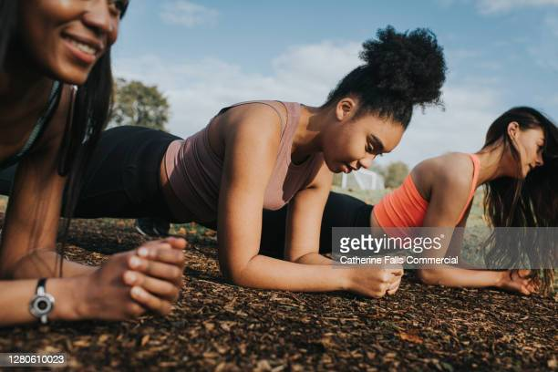 three woman in a sunny outdoor environment planking - togetherness stock pictures, royalty-free photos & images