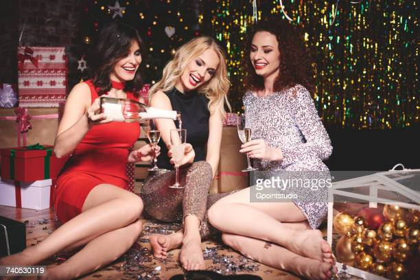 three woman sitting on floor at party, shoes off, surrounded by glitter, low section - christmas party stock photos and pictures